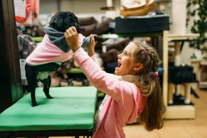 Little girl try on clothes for puppy in pet shop