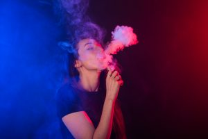Portrait of girl in colored neon smoke with vape or electronic cigarette