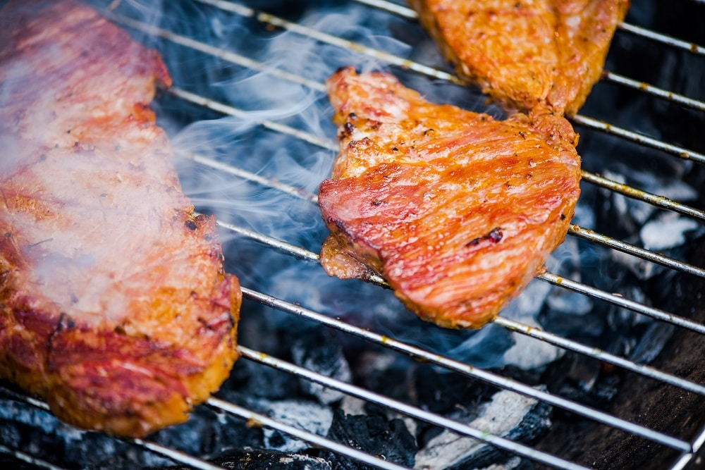 Close up view on meat on bbq hot grid grilling.