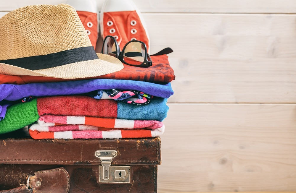 Travel preparation on an old suitcase - white wooden background - copy space
