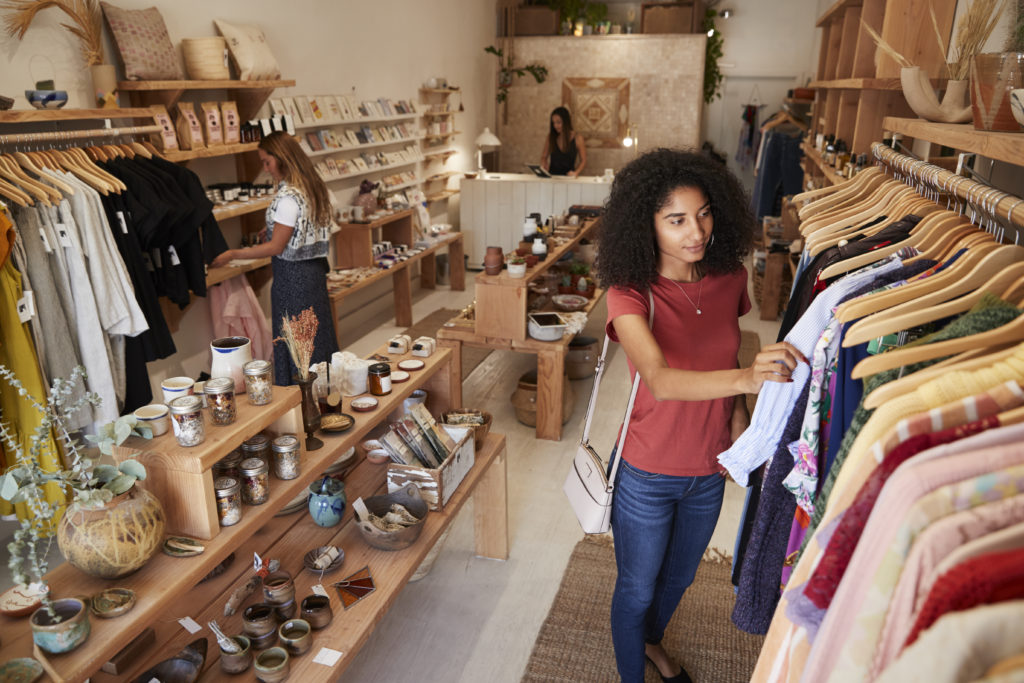 Customers Browsing In Independent Clothing And Gift Store